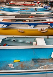 Side view of series of brightly colored boats moored at the harbor, street photography set at the lake