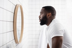 side view of serious afro-american man looking in mirror