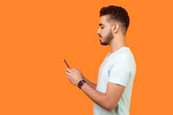 Side view of serious calm brunette man with beard in white t-shirt using cellphone, texting chatting in social media or surfing mobile web. empty copy space for advertisement, indoor studio shot