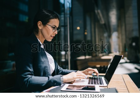 Side view of serious female economist working online with accounting documents on modern laptop device during sunny day in street cafeteria, caucasian businesswoman typing name for media files