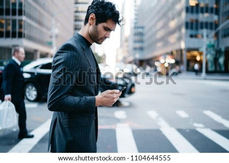 Side view of serious stylish businessman dressed in elegant outfit reading message on cellphone walking on pedestrian crossing, handsome prosperous male thinking about news on device using 4G internet