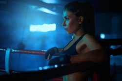 Side view of serious young professional female kickboxer wearing trendy sports outfit and bandages on hands. Fighter having rest after training, leaning on corner of ring. Concept of sport, boxing.