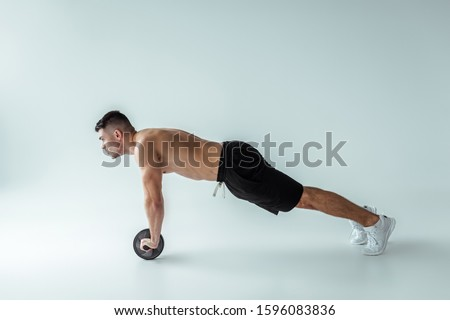 side view of sexy muscular bodybuilder with bare torso exercising with ab wheel on grey background