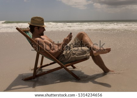 Side view of shirtless young man with hat relaxing on sun lounger and using mobile phone on beach in the sunshine