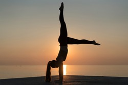 Side view of silhouette of a woman, standing on her hands. Healthy flexible girl doing yoga on sunrise. Girl practicing the handstand pose on tranquil beach at sunset during summer vacation in Spain.