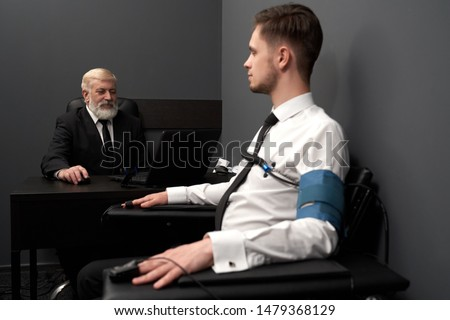 Side view of skilled man in black smart suit sitting at table and asking question to patient. Male in white shirt wearing pulse indicators answering and telling truth. Concept of lie detector. ストックフォト ©