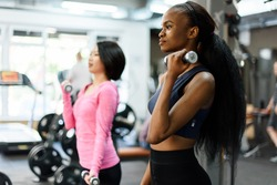 Side view of slim black african-american fitness instructor and asian lovely woman doing fitness exercise work with dumbbells together in the gym