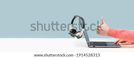 Side view of slim laptop and like thumb up hand. wireless headphones on grey desk. Blue background. Distant learning. working from home, online courses support. Audio podcast. vlogger blogger banner Stock fotó ©
