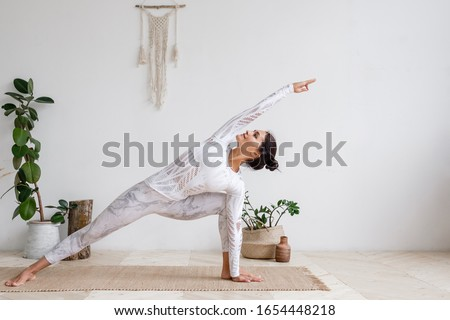 Side view of slim pretty positive young brunette woman doing Utthita parsvakonasana exercise, Extended Side Angle pose, on mat on floor surrounded by houseplants on white wall. Yoga and pilates