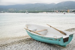 side view of small wooden fishing azure boat on pebble coast black sea beach in bad weather on sea, mountain and resort town background, horizontal stock photo image