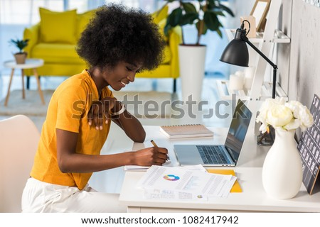 Photo of side view of smiling african american female freelancer working at home