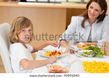 Side view of smiling boy sitting at the dinner table