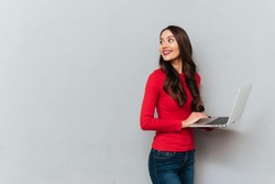 Side view of smiling brunette woman in red blouse holding laptop computer and looking back over gray background