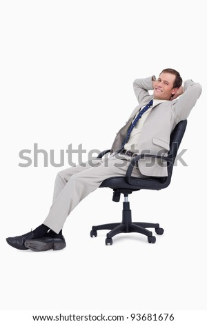 Side view of smiling businessman leaning back in his chair against a white background