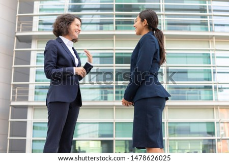 Side view of smiling colleagues standing on street. Cheerful young confident employees wearing formal suits looking at each other. Business confidence concept