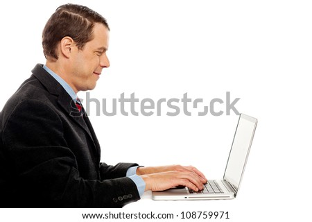 Side view of smiling corporate male typing on laptop isolated over white