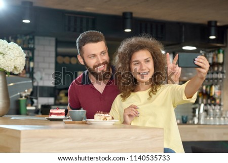 Side view of smiling couple taking selfie while date in cafe. Drinking fragrant coffee, eating delicious cakes, looking at smartphone, laughing. Boy wearing dark beard, girl having curly hair. #1140535733