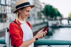 Side view of smiling female traveler in casual outfit with hat and backpack browsing mobile phone while chilling on embankment in Amsterdam