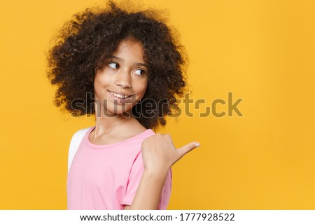 Side view of smiling little african american kid girl 12-13 years old in pink t-shirt isolated on yellow wall background studio. Childhood lifestyleconcept. Mock up copy space. Pointing thumb aside Stock photo ©