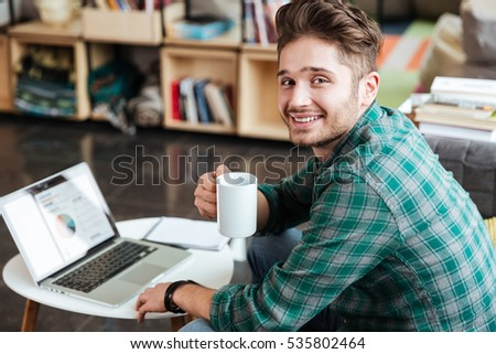 Side view of smiling man in green shirt sitting on sofa by the table with laptop and looking at camera. Coworking #535802464