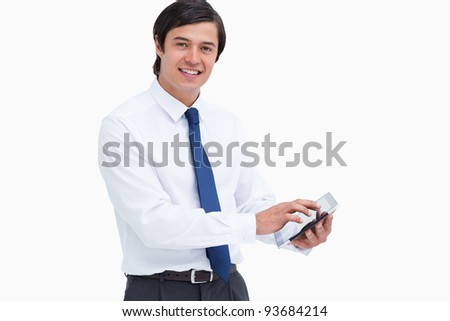 Side view of smiling tradesman with his tablet computer against a white background - stock photo