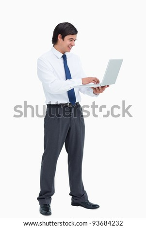 Side view of smiling tradesman working on his laptop against a white background