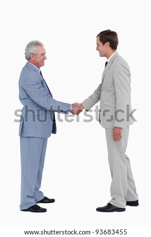 Side view of smiling tradesmen shaking hands against a white background