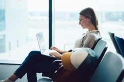 Side view of smiling young lady tourist in casual clothes and eyeglasses sitting at airport in front of window and typing on laptop while waiting for flight