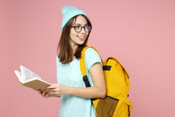 Side view of smiling young woman student in casual blue t-shirt hat glasses backpack reading book isolated on pastel pink color background studio. Education in high school university college concept