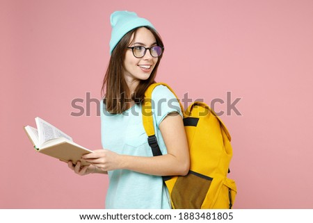 Side view of smiling young woman student in casual blue t-shirt hat glasses backpack reading book isolated on pastel pink color background studio. Education in high school university college concept Foto stock ©