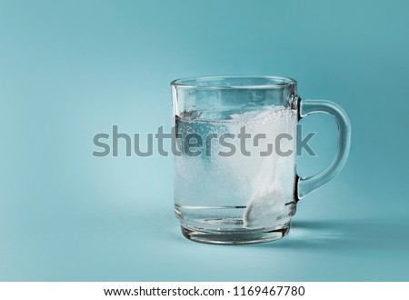 Side view of soluble pain killer dissolving bubbling in water, whole clear glass cup, isolated on blue background.