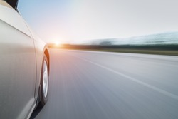 side view of speeding car with blurred road