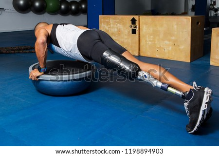 Side view of sportsman with artificial leg limb training in gym and doing push-ups on bosu ball