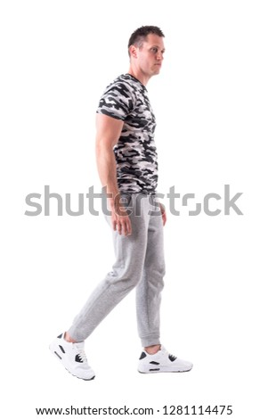 ab61608f1188 Side view of sporty fit confident man in sweatpants and army shirt walking.  Full body