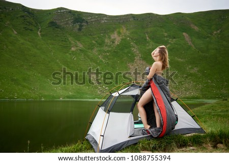 Side view of sporty naked woman standing in tent entrance in sleeping bag, beautiful view of lake in the mountains on the background. Camping lifestyle concept adventure summer vacations outdoor #1088755394