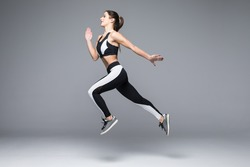 Side view of sporty young woman jumping isolated on grey background
