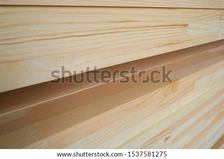 Side view of stack of three-layer wooden glued laminated timber beams from pine finger joint spliced boards for wooden windows
