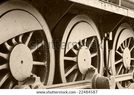 Side view of steam train wheels in sepia