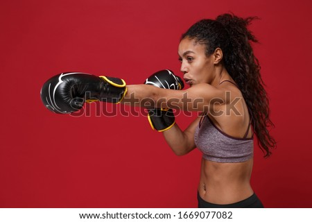 Side view of strong african american sports fitness boxer woman in sportswear working out isolated on red background. Sport exercise healthy lifestyle concept. Make boxing exercises in boxing gloves