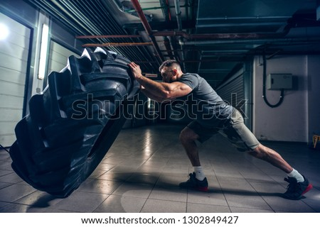 Side view of strong muscular Caucasian bodybuilder flipping massive tire in hallway. Night workout concept.