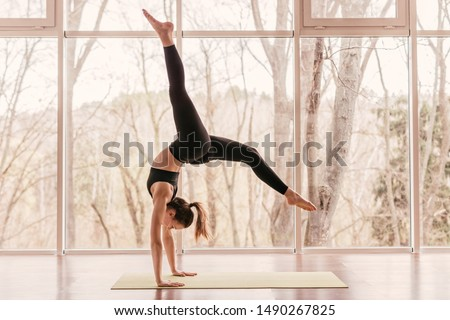 Side view of strong young lady in sportswear performing handstand with splits during morning yoga routine in gym