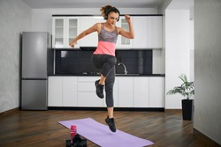 Side view of strong young woman jumping on mat in kitchen. Fit girl wearing sports outfit and headphones training at home in morning, listening to music. Concept of home cardio workout, weight loss.