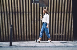 Side view of stylish positive middle aged female in jeans and sneakers strolling along street near modern building and drinking coffee