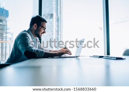 Side view of successful office worker sitting at table desktop in office company interior and using modern netbook for searching trade information, happy Caucasian male investor checking website news Stock photo ©