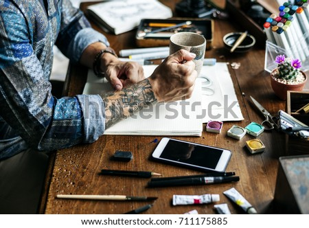 Side view of tattoo artist man working artwrok on wooden table