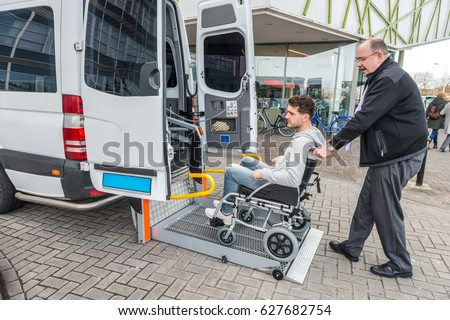 Side view of taxi driver assisting man on wheelchair to board van outside building