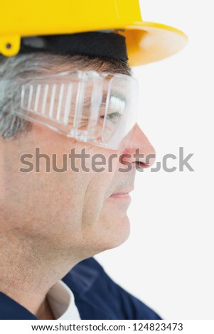 Side view of technician wearing protective eye wear and hardhad looking away over white background