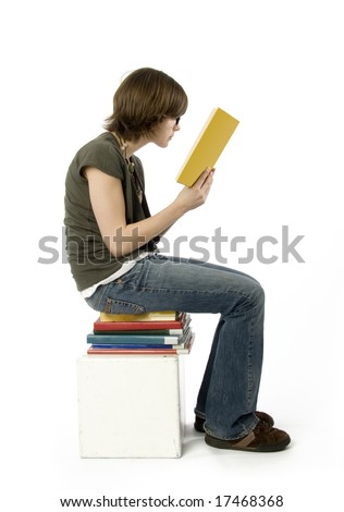 side view of teenage girl sitting on stack of books, reading.