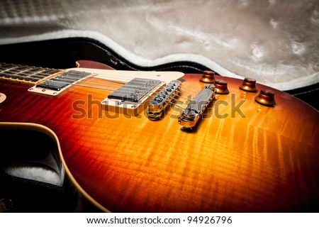 Side View of the Body of a Sunburst Electric Guitar Laying in a Hard Shell Electric Guitar Case