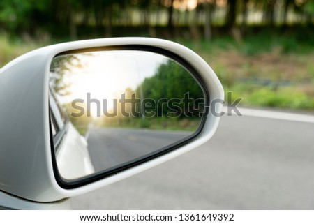 Side view of the car's glass on the road, asphalt and green forest in rural areas #1361649392